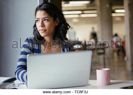 Nachdenklich Geschäftsfrau mit Laptop und trinken Kaffee Stockbild