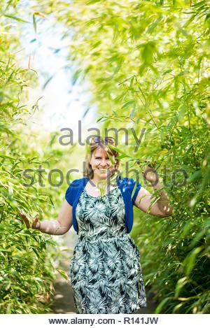 Eine junge Frau, die durch Bäume Stockbild