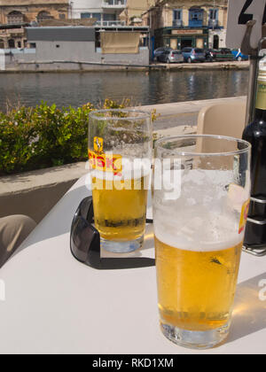 Halb voll - oder leere Gläser von cisk Bier auf einen freien Tisch in der Sonne, Urlaub auf Malta in der Nähe von Valetta Stockbild