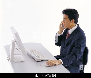 Büroangestellte, die auf einem Handy vor Computer sprechen Stockbild