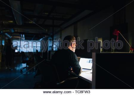 Geschäftsmanns, der spät am Laptop im dunklen Büro Stockbild