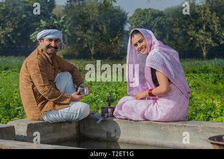 Gerne Landwirt Paar in der Nähe von Wasser Tank mit Essen in ihrer Landwirtschaft Feld. Stockbild