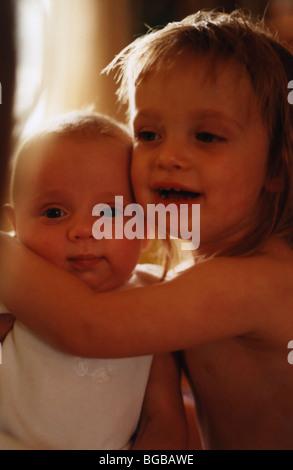 Fotografie des jungen Schwestern kuscheln Baby Kleinkinder-Kinder-Familie Stockbild