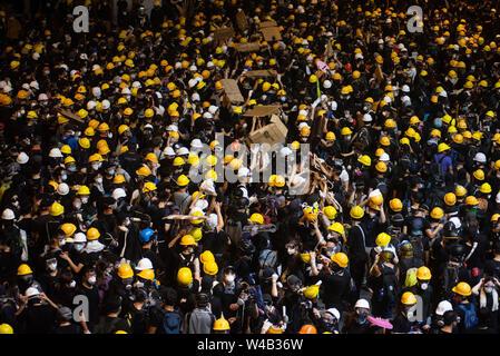 Die Demonstranten hetzt Zurück nach Polizei Tränengaskanister Gang mit Sonnenschirmen und Barrikade bauen wie Tausende Demonstranten Teil einer Grosskundgebung fordert unabhängige Untersuchung Polizei Taktik in Hong Kong. Stockbild