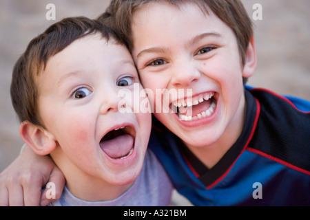 Brüder beieinander stehen und lachen Stockbild