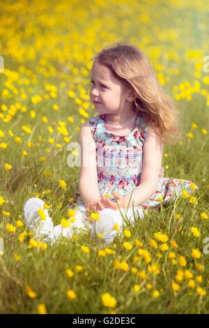 3-jähriges Mädchen sitzen auf einer Wiese mit gelben Blüten Stockbild
