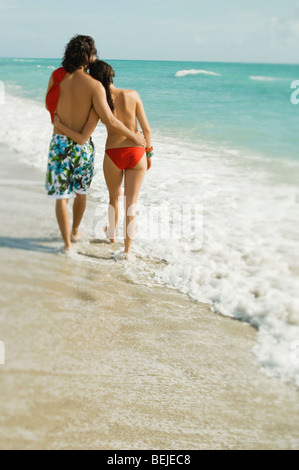 Rückansicht eines jungen Paares, walking am Strand Stockbild