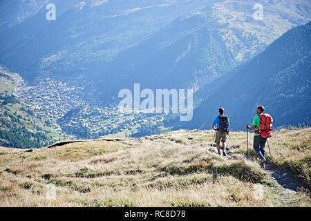 Wanderer auf grasigen Felsen mit Blick auf das Tal, Mont Cervin, Matterhorn, Wallis, Schweiz Stockbild