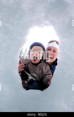 Mutter und Sonne spielen im Schnee Stockbild