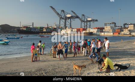 Die Einheimischen am Strand mit einem Containerschiff Ausfahrt aus dem Hafen hinaus, Santa Marta, Magdalena, Kolumbien Stockbild