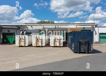 Weiß Müllcontainer stehen auf einem Fabrikgelände, und es gibt andere Müllcontainer neben ihnen Stockbild