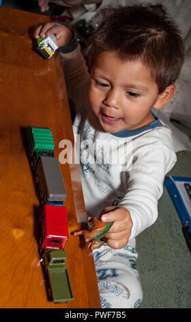 Vorschulalter Hispanic junge spielt mit Miniatur Zug am Weihnachtsmorgen. Herr © Myrleen Pearson... Ferguson Cate Stockbild