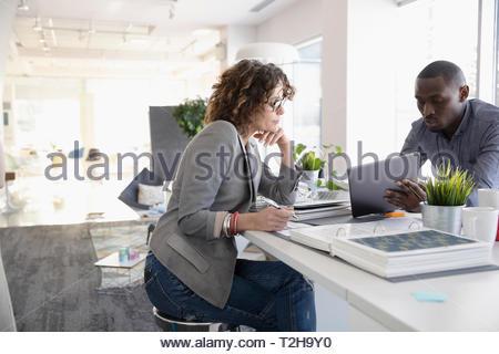 Innenarchitekten mit Laptop im Büro Stockbild