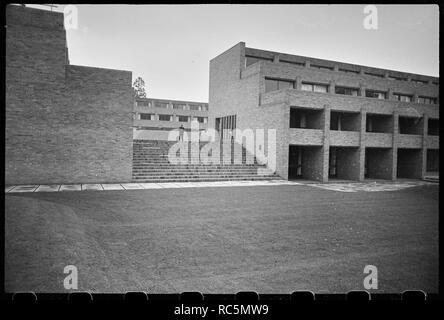 Harvey, Gonville und Caius College, Universität Cambridge, Cambridgeshire, c 1955 - c 1980. Außenansicht von Harvey Hof, Studentenwohnheime, die sich um einen quadratischen Innenhof, gesehen aus dem Süden angehoben und die Suche nach der Treppe in der Süd-West-Ecke des Hofes. Die Unterkunft wurde von Sir Leslie Martin und Colin St. John Wilson zwischen 1960 und 1962 integriert. Die website ist überwiegend Ziegel mit einige bronze Verkleidungen und das Bild zeigt vertikale Holz Verkleidungen an der Seite des Gebäudes am oberen Ende der Treppe. Das Gebäude ist drei Stockwerke mit einem Untergeschoss, und die Zimmer sind staggere Stockbild