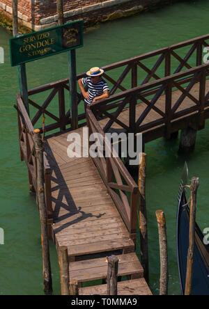 Hohe Betrachtungswinkel eines Gondoliere auf einem Ponton aus Holz, Region Veneto, Venedig, Italien Stockbild