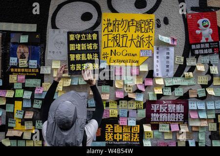 Eine Frau Klebstoffe ein Poster mit Nachrichten, die gegen die Auslieferung Bill und pro-Demokratie in einem Lennon-mauer in Wan Chai. Hong Kong Demonstranten versammelten für ein weiteres Wochenende der Proteste gegen die umstrittene Auslieferung Rechnung und mit einer wachsenden Liste von Beschwerden, die der Aufrechterhaltung des Drucks auf Chief Executive Carrie Lam. Stockbild