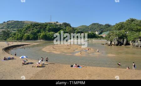 Menschen Paddeln in und Sonnenbaden am Rio Barbadun auf La Arena Strand, Pobena, in der Nähe der Muskiz, Vizcaya/Bizkaia, Spanien, August. Stockbild