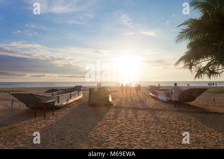 Ahungalla, Sri Lanka, Asien - Traditionelle Langboote in Induruwa Beach bei Sonnenuntergang Stockbild