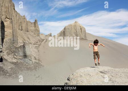 Junge springt auf Sanddünen Stockbild