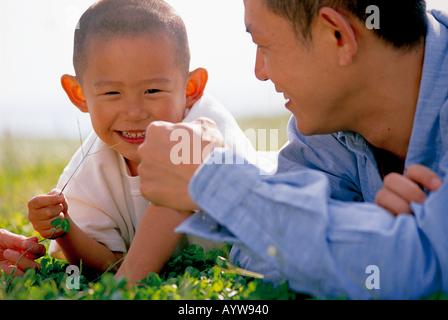 Liegend auf der Wiese mit seinem Sohn Vater Stockbild