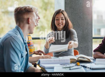 Junge Leute sitzen am Tisch freigeben von Notizen für Schule Zuordnung. Gruppe von Studenten zusammen in einer Stockbild