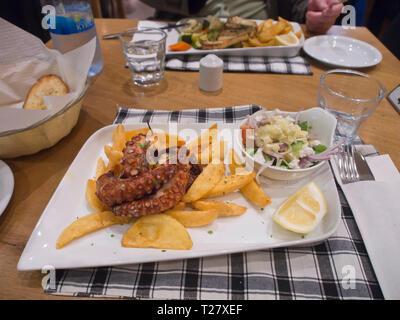 Mediterrane Küche, gegrilltem Tintenfisch mit Kartoffeln und Salat, auf einem Tisch im Restaurant in Ayia Napa Zypern Stockbild