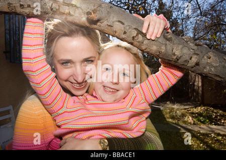 Eine Mutter umarmte ihre Tochter, die von einem Ast hängend Stockbild