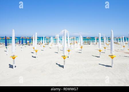 Alimini Grande, Apulien, Italien - gefaltet Sonnenschirme am schönen Strand von Alimini Grande Stockbild