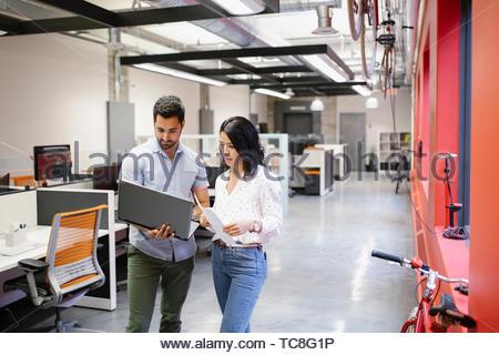 Geschäftsleute mit Laptops und Schreibarbeit im Großraumbüro Stockbild