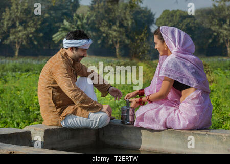 Gerne Landwirt Paar in der Nähe von Wasser Tank Essen in ihrer Landwirtschaft Feld zu haben. Stockbild