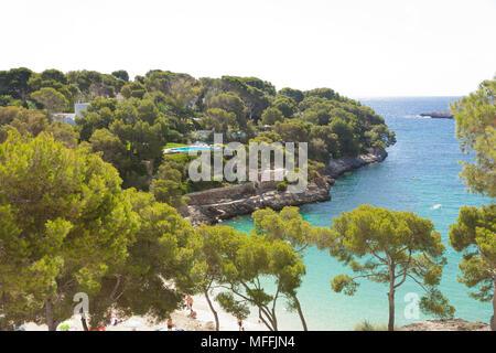 Cala d'Or, Mallorca, Spanien - August 2016 - ein Blick auf den Strand von Cala d'Or durch ein paar Bäume Stockbild