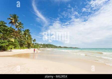 Mirissa Beach, Sri Lanka, Asien - Dezember 2015 - Touristen zu Fuß auf den Sand und genießen die Aussicht Stockbild