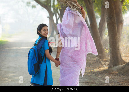 Rückansicht eines ländlichen Frau Brennholz tragen auf dem Kopf gehen mit ihrer Schule Tochter im Dorf. Stockbild