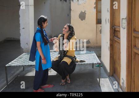 Happy Village Frau sitzt auf einem Feldbett sprechen über Mobiltelefon halten sie die Hand ihrer Tochter. Stockbild