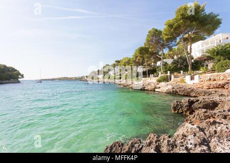 Cala d'Or, Mallorca, Spanien - eine felsige Küste und türkisblaues Wasser am Strand von Cala d'Or Stockbild