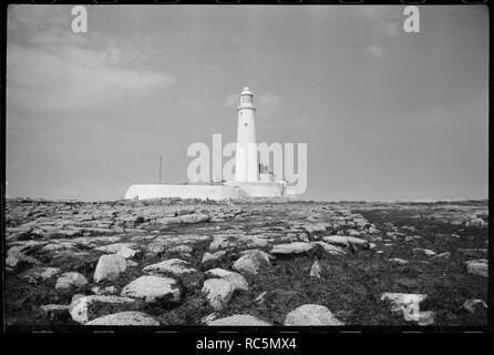 St Mary's Leuchtturm, Whitley Bay, North Tyneside, c 1955 - c 1980. Eine Außenansicht des 19. Jahrhunderts Leuchtturm, mit dem 126 m hohen Turm mit seitlichem Cottage der Keeper auf der rechten Seite, und ein Stein Mauer rund um den Komplex, von Osten gesehen. Der Turm der Leuchtturm ist ein weißes gerendert Tower 126 m hoch, mit Kuppeln Dach und weathervane. Die Fenster sind im gesamten Turm verstreut, und die Fenster der Laterne Zimmer an der Spitze haben diagonal Scheiben. Cottage der Keeper unten ist eine steinerne Gebäude, weiß gestrichen und mit dem Turm von einem modernen 1-stöckigen verknüpft lief Stockbild