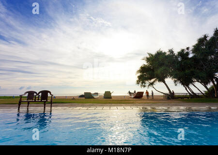Ahungalla, Sri Lanka - Dezember 2015 - ein Hotel Pool Blick auf Silhouetten zu Fuß in Richtung Strand bei Sonnenuntergang Stockbild