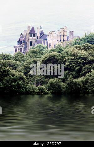 ein altes Märchenschloss am Ufer eines Sees Stockbild