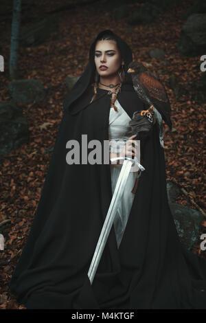Stolz mit Kapuze Frau mit Schwert und Hawk. Wald Hintergrund Stockbild