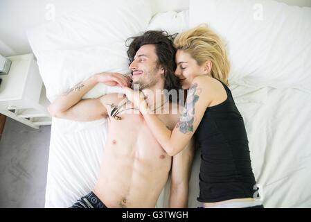 Eine coole junge tätowierte paar auf einem Bett kuscheln. Stockbild