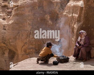 Ein junger Beduine junge bereitet sich sorgfältig ein dampfendes warmes Essen und Kaffee unter den Augen seiner Mutter an der Basis von einem entfernten Höhle in Petra in Jordanien. Stockbild