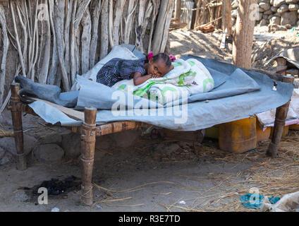 Äthiopischen Mädchen ruht auf einem Bett vor ihrem Haus, Von ferne Region, Assayta, Äthiopien Stockbild