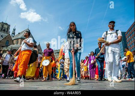 """Eine Frau fegt die Straße wie sie Teil während der Zeremonie dauert. Das Festival der Wagen, auch bekannt als Ratha Yatra, ist ein zeitloses Festival, mit Ursprung in der antiken Stadt Jagannatha Puri in Indien. Seit Tausenden von Jahren, haben zu Jagannatha Puri wurde in Indien in das älteste Festival der Welt namens Ratha-yatra"""", den Wagen Festival"""". Jetzt Ratha-yatra wird jedes Jahr in Dutzenden von Städten rund um die Welt abgehalten. Das ratha Yatra Festival hat einen gemeinsamen Blick in den meisten großen Städten der Welt werden seit 1968 durch die ISKCON, Hare Krishna Bewegung. In Rotterd Stockbild"""