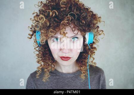 Junge blonde Frau ist das Hören von Musik mit Ihrem Kopfhörer Stockbild