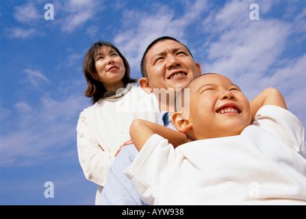 Eltern und ein Junge mit blauer Himmelshintergrund Stockbild