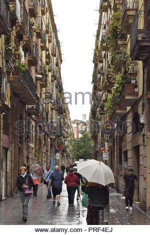 Straße mit Wohnimmobilien, Menschen zu Fuß durch El Raval an regnerischen Tag, Ciutat Vella, Barcelona Spanien Europa. Stockbild