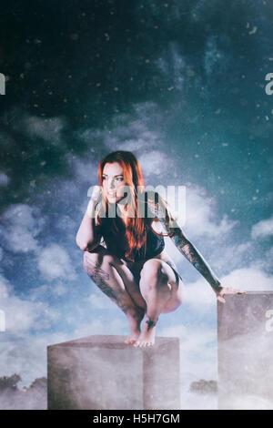 Rote Haare Frau kauert auf eine Reihe von weißen Felder Stockbild