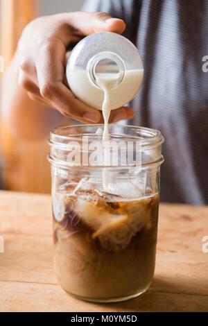 Afrikanische amerikanische Frau gießen Milch in jar von Kaffee Stockbild