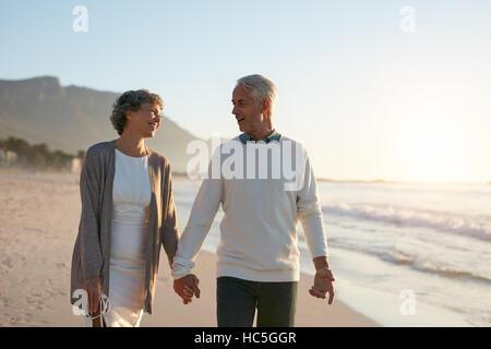 Porträt des romantischen älteres Paar gehen Hand in Hand am Strand. Älteres Paar mit einem Spaziergang Stockbild