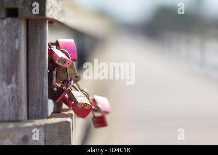 Graviert Vorhängeschlösser hängen auf einer Brücke als Symbol für Liebhaber Stockbild